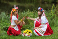 Girls on the banks of the river two in ukrainian costumes dressed for holiday ivan kupala sitting bank and drink vodka Stock Image