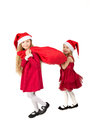 Girls in the bell santa claus dragging a bag of gifts two red dress Royalty Free Stock Photos