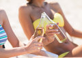 Girls in bikinis with drinks on the beach chairs Stock Photography