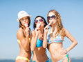 Girls in bikinis with ice cream on the beach summer holidays and vacation eating Royalty Free Stock Photos