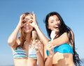 Girls in bikinis with ice cream on the beach summer holidays and vacation eating Royalty Free Stock Image