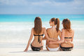 Girls in bikinis sunbathing sitting on the beach three young with a nice figure two black one white bikini sun glasses arm Stock Photo