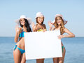 Girls with blank board on the beach summer holidays and vacation in bikinis holding white Royalty Free Stock Image