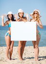 Girls with blank board on the beach summer holidays and vacation in bikinis holding white Stock Photo