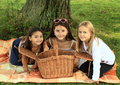 Girls on blanket with basket three curious sitting under the tree watching an opened picnic Stock Photo