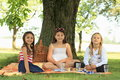 Girls on blanket having picnic three happy sitting under the tree and Stock Photos