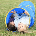 Girls in blue kids tunnel little lying for Royalty Free Stock Photos
