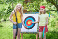 Girls with bow near sport aim in sunny summer day Stock Images