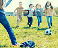 Girls and boy playing soccer in park in autumn Royalty Free Stock Photo