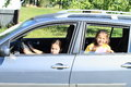 Girls in car smiling little girl driving a silver her sister watching thru opened window Stock Photos