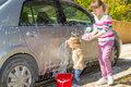 Girls car washing cute young are helping their parents by the Stock Image