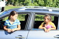 Girls in car windows smiling little watching thru opened window of a silver Royalty Free Stock Photography