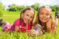 Girls caught butterfly close up of two happy little nine years old hold jar with laying in the grass and showing big smile on Stock Images