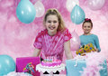 Girls celebrating a birthday having fun at party in front of cake and presents Stock Photography