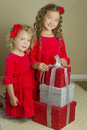 Girls with christmas holiday presents two sisters curls in their hair and dressed in red velvet dresses matching red bows in their Stock Photography
