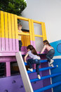 Girls climbing playhouse ladder full length of little while boy looking at them Stock Image