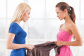 Girls confrontation side view of two angry young women holding one dress together and looking at each other Stock Images