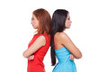 Girls confrontation two beautiful young women standing back to back and keeping arms crossed while isolated on white Stock Photo