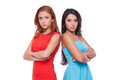 Girls confrontation two confident young women standing close to each other and keeping arms crossed while isolated on white Stock Image