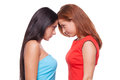 Girls confrontation two young women standing face to face and looking at each other while isolated on white Stock Images
