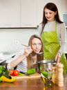 Girls cooking together at kitchen domestic focus on blonde Royalty Free Stock Image