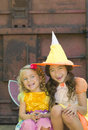 Girls in costume halloween two happy smiling sisters sit and laugh as they celebrate the holiday of dressed colorful costumes as a Royalty Free Stock Photos