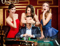 Girls cover the eyes of the gambler Stock Photography