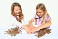 Girls dividing money two kids savings of czech crowns small change in hands Stock Photos