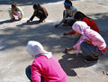 Girls drawing with chalk playing a game at playground at school young children using white arab muslim female teacher Stock Photo