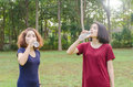 Girls drinking water after excercise two asian from bottle Royalty Free Stock Photos