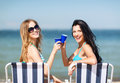 Girls with drinks on the beach chairs summer holidays and vacation in bikinis Royalty Free Stock Image