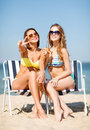 Girls with drinks on the beach chairs summer holidays and vacation in bikinis Stock Photos