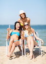 Girls with drinks on the beach chairs summer holidays and vacation in bikinis Stock Images