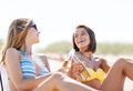 Girls with drinks on the beach chairs summer holidays and vacation in bikinis Stock Photo