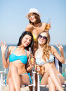 Girls with drinks on the beach chairs summer holidays and vacation in bikinis Stock Image