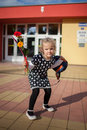 Girls first day at school girl stood outside for her with bag and bunch of flowers Royalty Free Stock Images