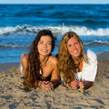 Girls friends having fun happy lying on the beach sand shore Stock Photos
