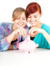 Girls friends with piggy bank Stock Photos