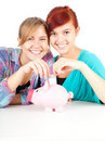 Girls friends putting five euro to piggy bank Stock Image
