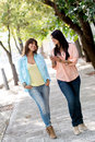 Girls going for a walk outdoors and looking at their mobile phone Stock Image