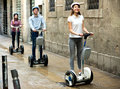 Girls and guy traveling through city by segways attractive Stock Photo