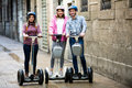 Girls and guy traveling through city by segways smiling Stock Photos