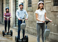 Girls and guy traveling through city by segways two beautiful Royalty Free Stock Photos