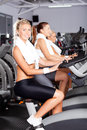 Girls on gym bike Stock Images