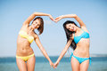 Girls having fun on the beach summer holidays and vacation making heart shape with hands Royalty Free Stock Photos