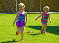 Girls having fun with sprinkler in garden Royalty Free Stock Photo
