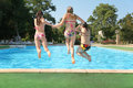 Girls jump in pool Stock Images