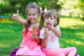 Girls kids sisters friends teasing eating ice cream showing off tongues sitting on grass thumb up focus on younger girl s face Royalty Free Stock Images
