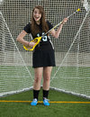 Girls lacrosse player goofing around in the gate high school atrums her stick like it s a guitar as she stands on a playing field Stock Photo