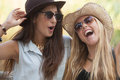 Girls laughing having fun in summer with hats and sunglasses Royalty Free Stock Photos